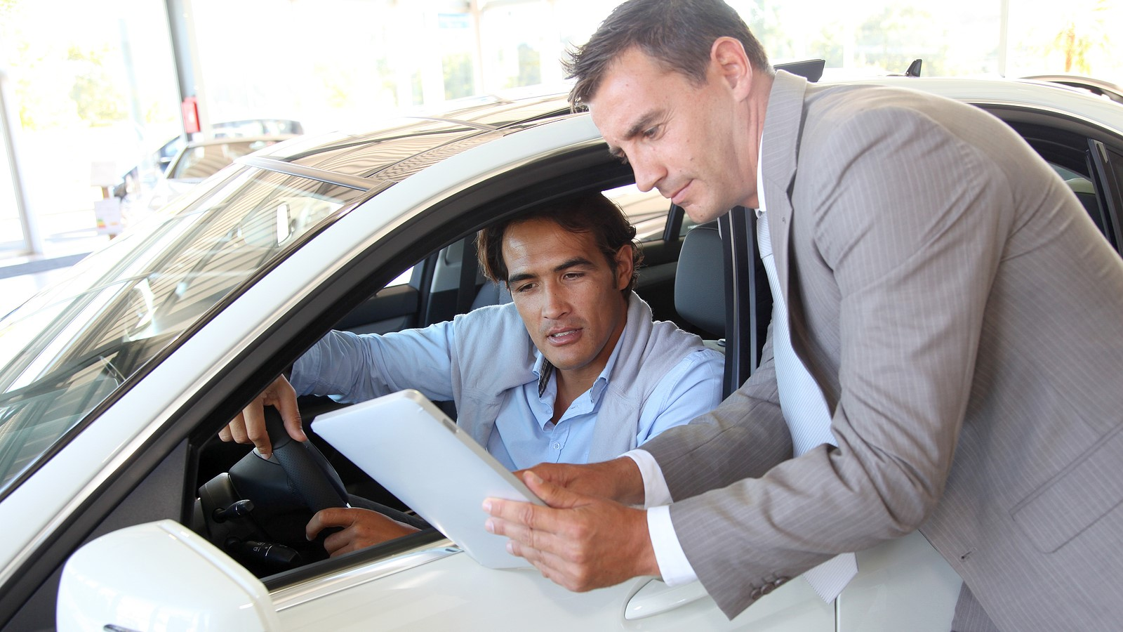 a male buyer working with a car salesman on the best way to finance his new car