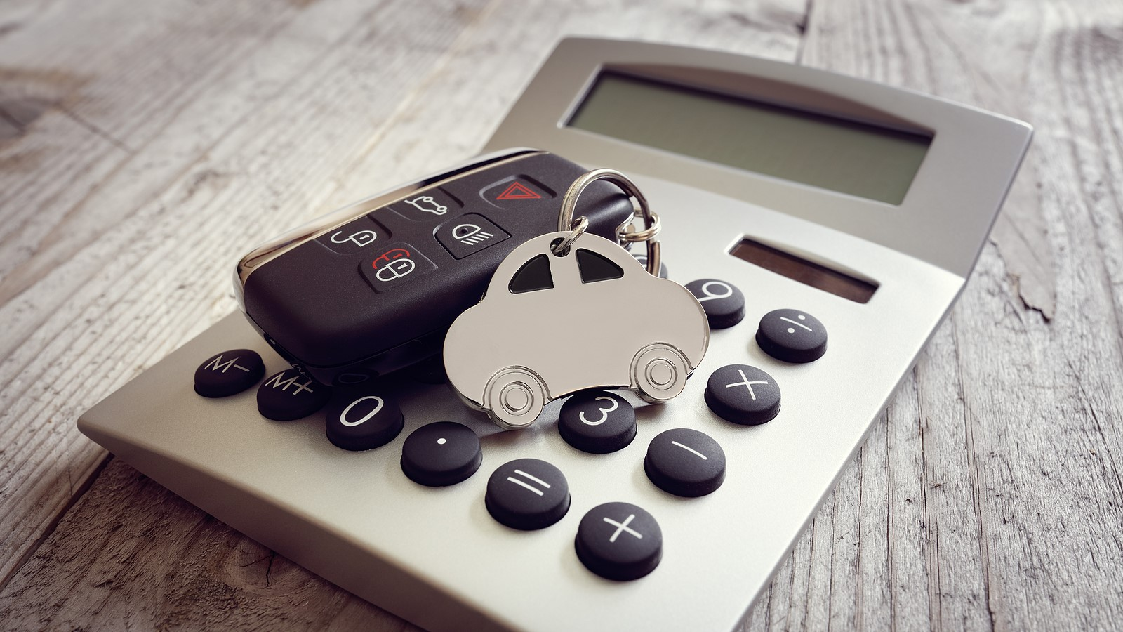 a set of car keys on top of a calculator representing how to pay off a car loan faster