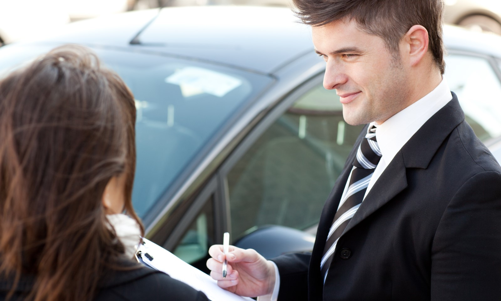 a woman working with a car salesman at the dealership to finalize her car loan