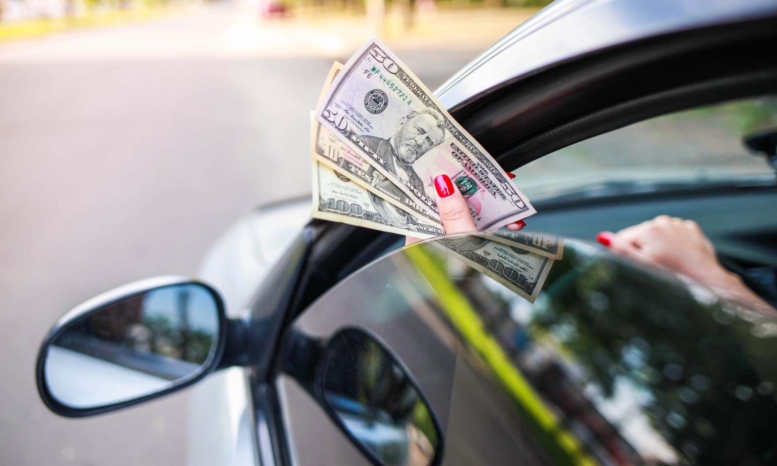 a woman holding money out her car window representing saving money by refinancing a car loan