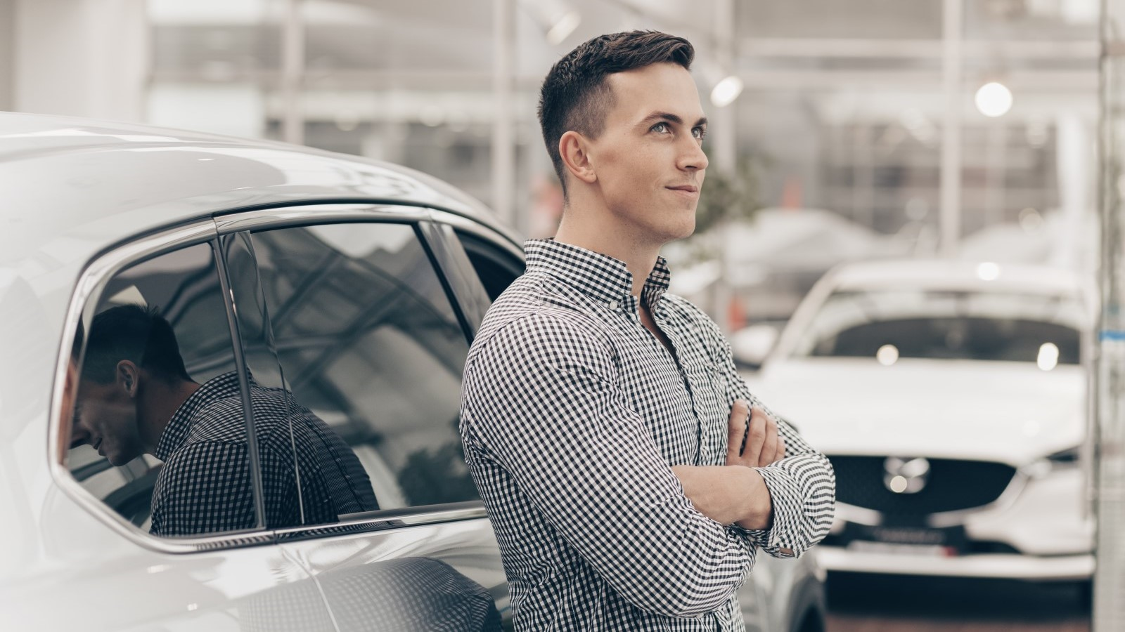a man leaning against a car at the dealership looking like he's thinking hard about his purchase