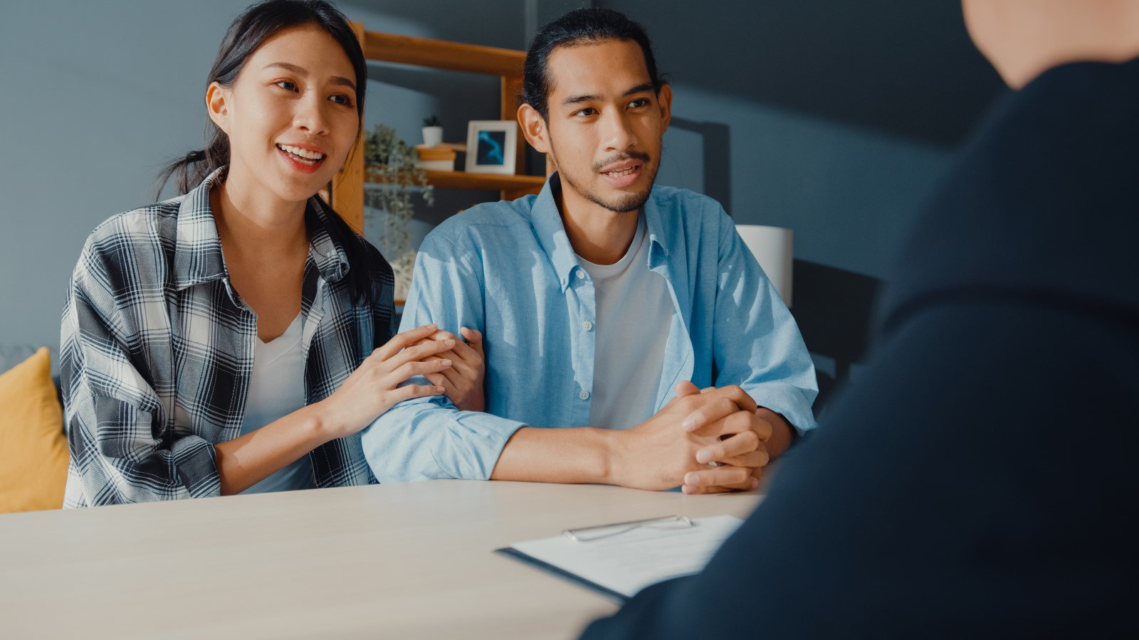A young Asian couple discusses loan options with their lender.