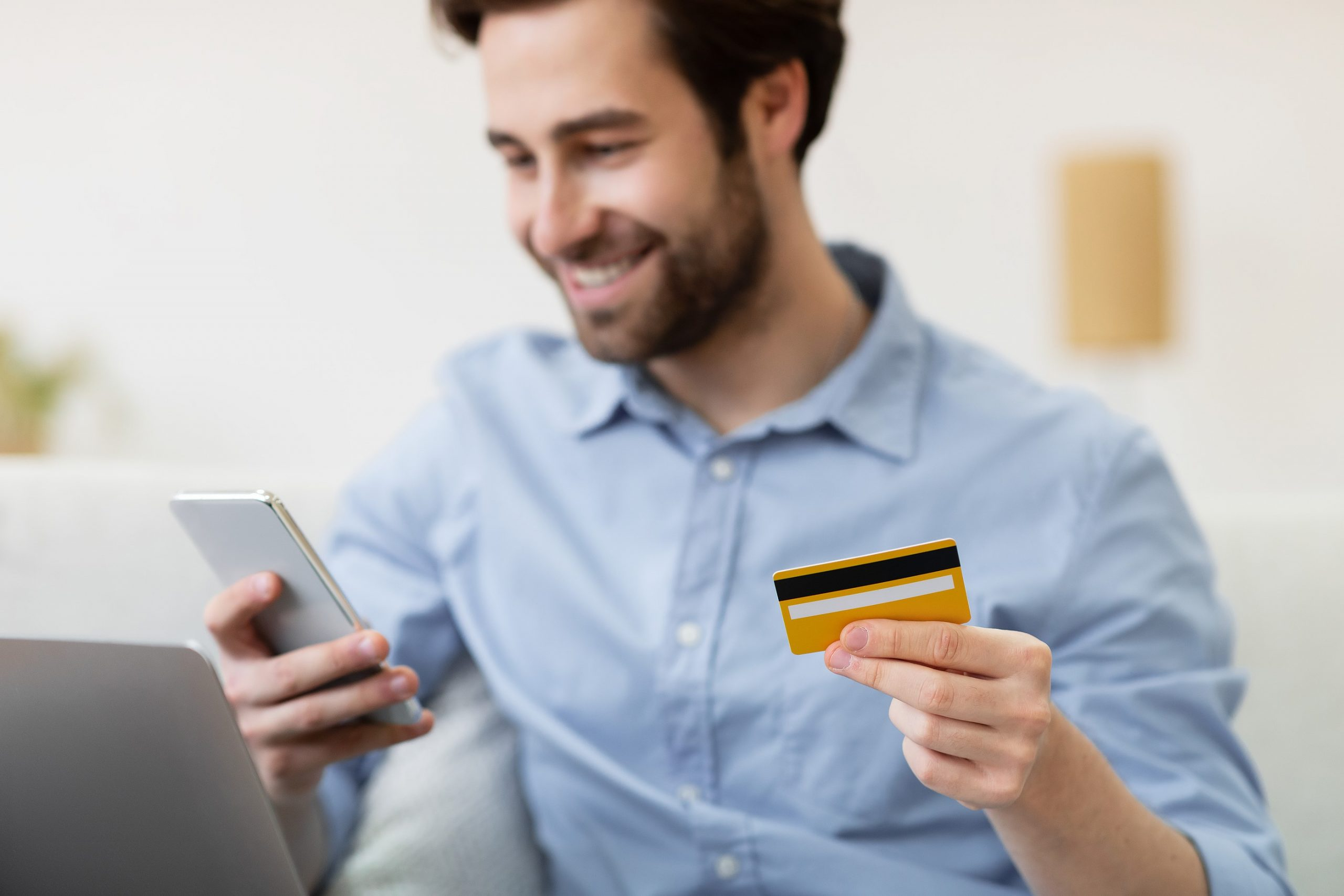 Young, smiling man holds atm card and looks at phone.  Learn about personal saving account rates at GHS FCU.