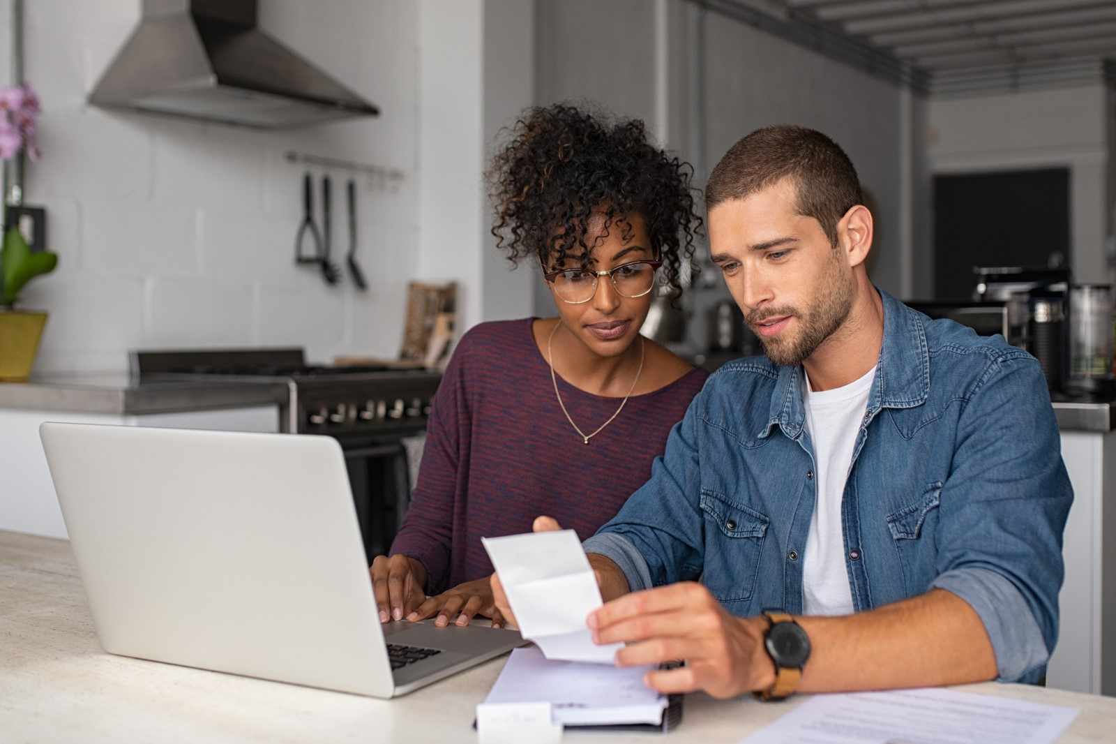 a man and woman look at their bank account to see about refinancing their mortgage.